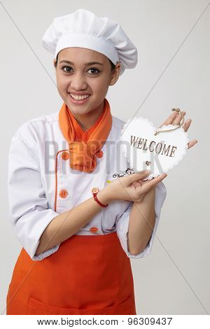 Indian woman with chef uniform holding a welcome signage