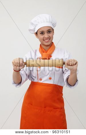 Portrait of a Indian woman with chef uniform holding rolling pin