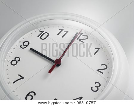 Close up of an analog clock at 9 o'clock