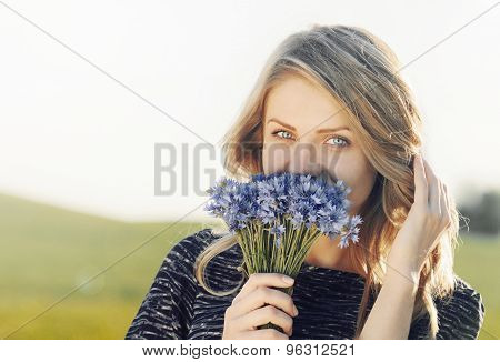 Portrait Of A Beautiful Young Cheerful Woman With Cornflowers