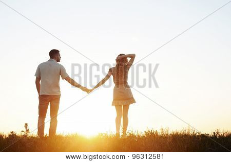 Stunning Sensual Young Couple In Love Posing In Summer Field At The Sunset