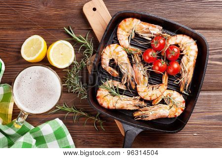 Grilled shrimps on frying pan and beer. Top view