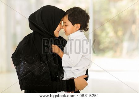 adorable middle eastern woman playing with her son at home