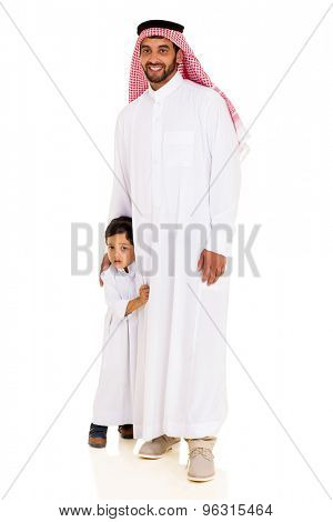 handsome muslim man standing with his shy son
