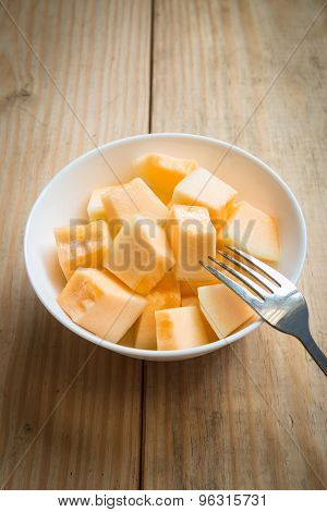 Cantaloupe In White Dish With Fork On Wood Background