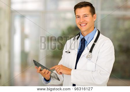 happy healthcare worker using tablet computer at hospital