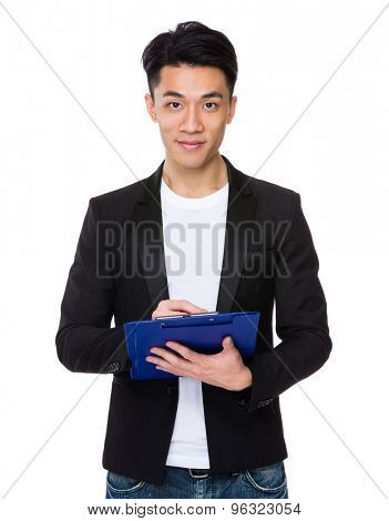 Young businessman take note on clipboard