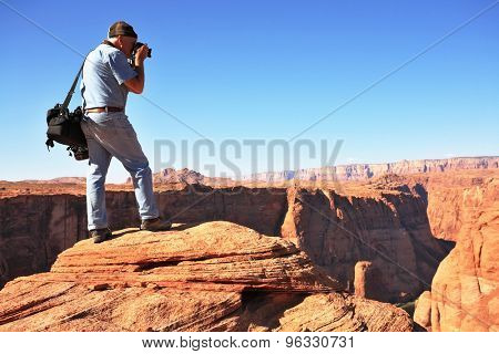 Professional photographer photographed on a steep and high bank of the river. The famous Colorado River in the picturesque Horseshoe bend.