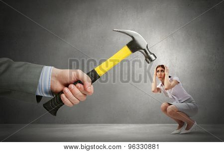 Close up of hammer in male hand attacking scared woman