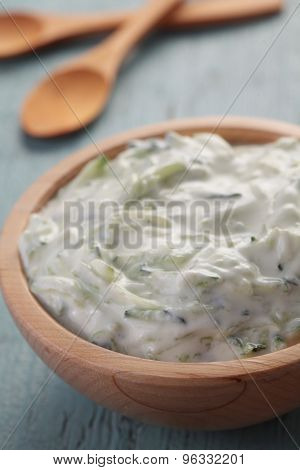 Tzatziki in a wooden bowl on a rustic table