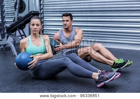 Portrait of muscular couple doing abdominal ball exercise