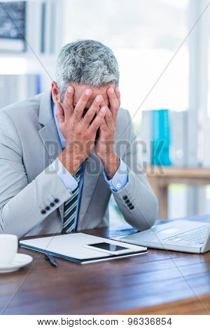 Depressed businessman with hands on head in office