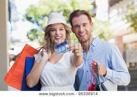 Portrait of a cute couple showing a credit card