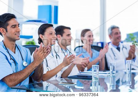 Doctors applauding while sitting at a table in medical office