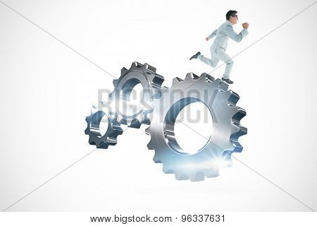 Geeky happy businessman running mid air against metal cog and wheel connecting