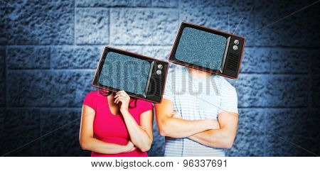 Young couple with bags over heads against dark grey room