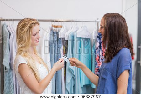 Friendly girls handing a credit card in the clothing store