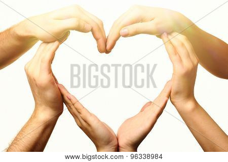 Heart formed by male and female hands on light background