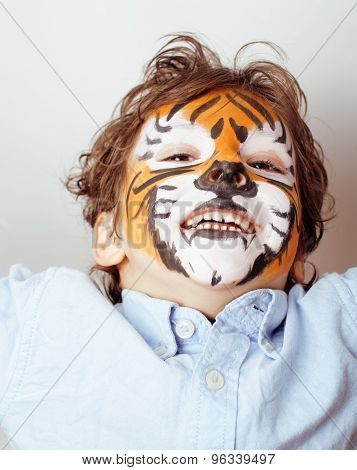 little cute boy with faceart on birthday party close up, tiger