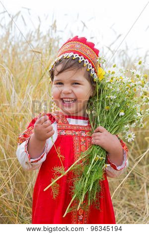 Laughing Little Girl In The Russian National Sundress With A Bouquet Of Camomiles