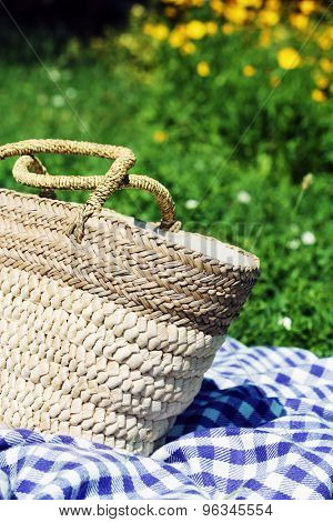 Wicker basket and Plaid for picnic on green grass