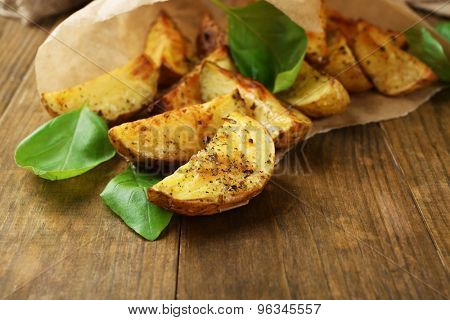 Baked potatoes in parchment on wooden table, closeup