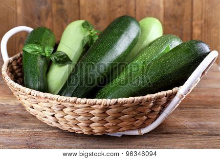 Fresh zucchini with squash and basil in wicker basket on wooden background