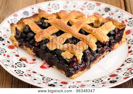 Piece Of Triangular Homemade Lattice Pie With Whole Wild Blueberries In White Plate