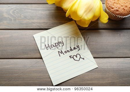 Fresh cupcake, tulips and Happy Monday massage on wooden background