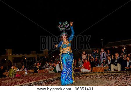 Belly Dancer Performing In Front Of A Crowd In Arabian Desert
