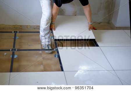 worker carries a floating floor on steel feet