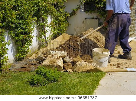 Gardener digging over soil in an garden