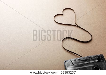 Audio cassette with magnetic tape in shape of heart on brown background