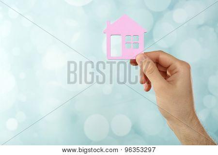 Female hand holding house on light blurred background