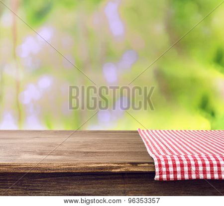 Empty wooden table with napkin on bright background