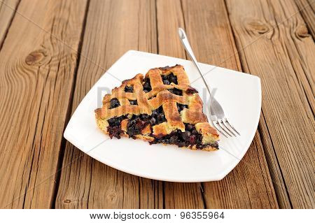 Piece Of Delicious Homemade Lattice Pie With Whole Wild Blueberries In White Plate With Fork