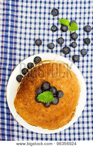 pancakes with fresh blueberries on a table