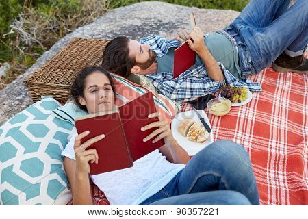 happy and relaxed couple enjoying a picnic on the rocks, near the ocean, reading a book