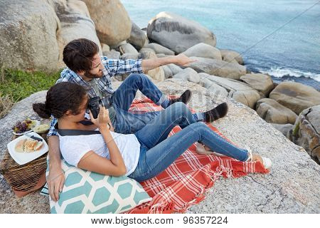 Happy and romantic couple, having a picnic on the rocks, taking pictures of the ocean