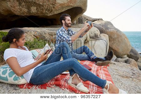 happy couple enjoying a picnic on the rocks, near the ocean, reading and taking pictures