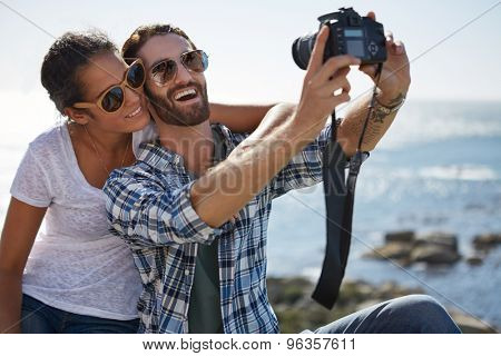 couple takes a selfie with a beautiful ocean background using a digital camera
