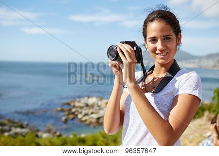 young, attractive woman stands near the ocean and poses for a pic with digital camera in her hand