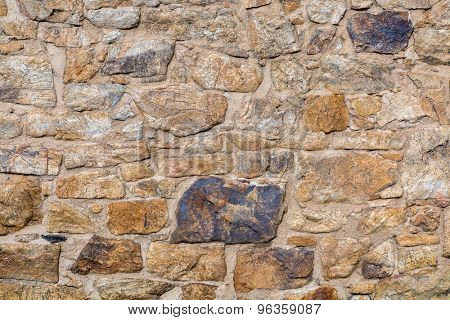 background and texture of old stone wall built with irregular sandstone blocks