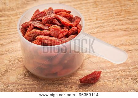 measuring scoop of dried goji berries against cedar wood plank