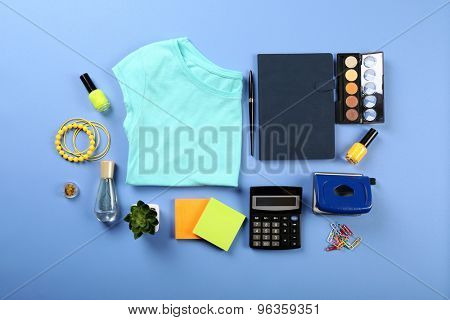 Female shirt, cosmetics and office details on color table, top view