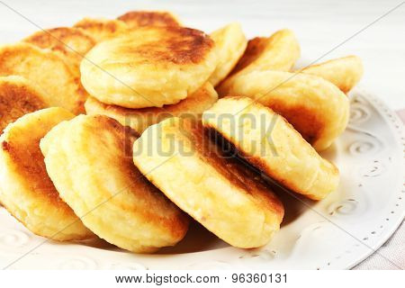 Fritters of cottage cheese in plate, closeup
