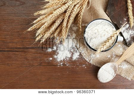 Whole flour with wheat on wooden table, top view