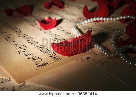 Beautiful rose petals with pearls in dark on music sheets, closeup