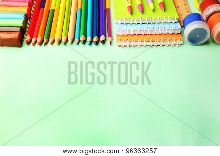 Colorful school stationery on green background