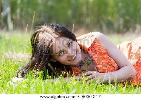 Pretty girl in orange dress laying on grass